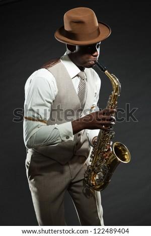 Black american jazz saxophone player. Vintage. Studio shot. - stock photo