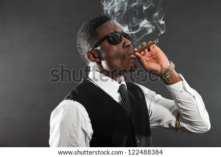 Black american mafia gangster man in suit smoking cigar. - stock photo