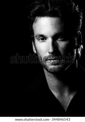 Black an white portrait of handsome mid-adult man wearing black, looking at camera confidently.