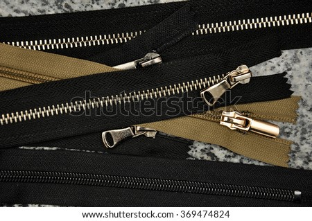 Black and brown zipper close up. Many black zippers background. - stock photo