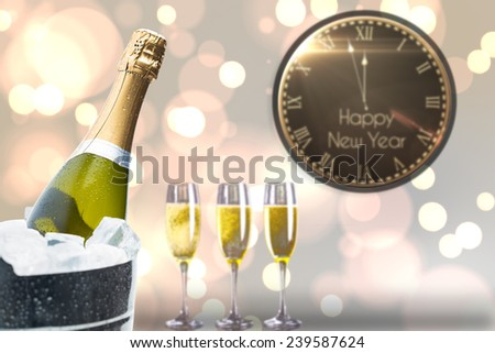 Black and gold new year message against champagne cooling in ice bucket - stock photo