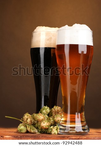 black and golden beer in glasses and hop on wooden table on brown background - stock photo