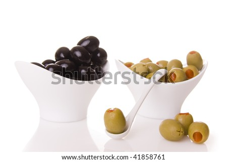 Black and green olives isolated on white - Focus on the olive on ten spoon - stock photo