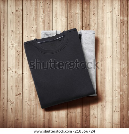 Black and grey jumpers on wood background - stock photo