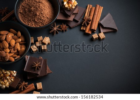 Black and milk chocolate, cocoa powder, nuts, sweets, spices and brown sugar on a black background, food concept - stock photo
