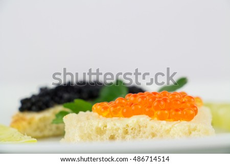 Black and red caviar on roasted bread served on white plate. Studio shot, isolated on white.