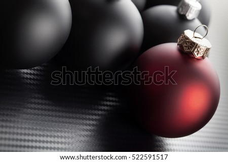 Black and red christmas baubles on carbon background