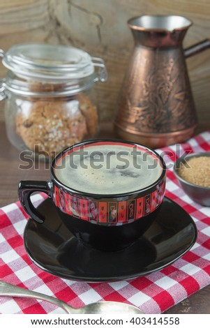 Black and red cup of coffee, red and white checkered napkin, coffee pot, sugar and oatmeal cookies in a glass jar on a dark wooden background