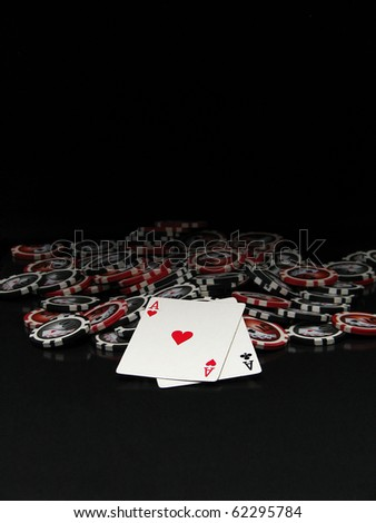 Black and red poker chips and cards isolated on black background