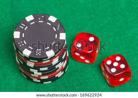 black and red poker chips and dice on a green casino felt