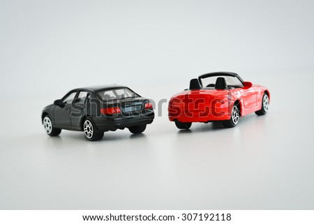Black and red toy cars on white background suggesting a competition - stock photo
