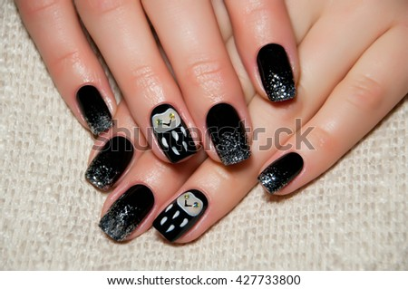 black and silver nail polish with an owl on the ring finger - stock photo
