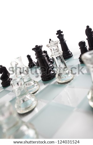 Black and transparent glass chess pieces, on a see through chessboard.