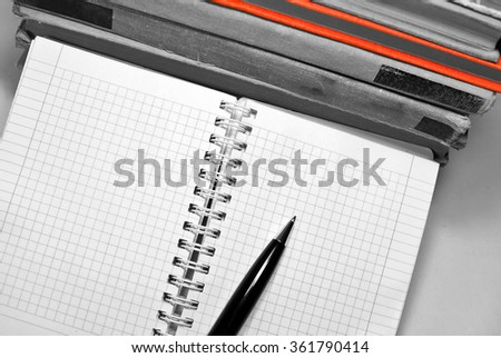 Black and white aged books with notebook, pen and red book. - stock photo