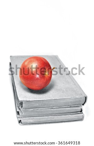 Black and white aged books with red apple.  - stock photo