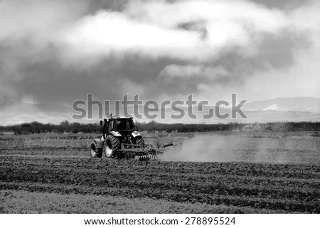 black and white agricultural background with fields and tractor  - stock photo
