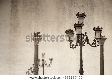 Black and white antique effect ,pigeons on street lamps, with blurred background, Venice Italy - stock photo