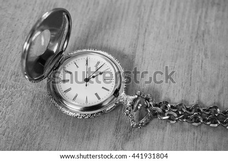 black and white art photography monochrome, open pocket watch and chain lie on a light wooden table background, arrow on the clock - stock photo