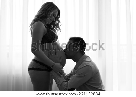 Black and white artistic contre-jour picture of a pregnant woman and her husband kissing and touching her belly - stock photo