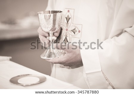 Black and white artistic digital photo of Catholic priest in church wedding marriage ceremony. - stock photo