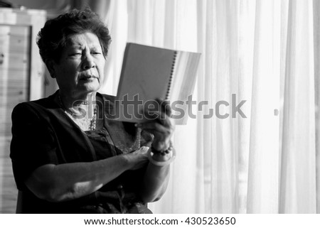 Black and white Asian senior woman reading a book with window light shadow.