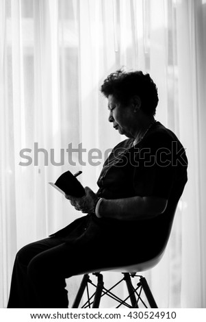 Black and white Asian senior woman  with holding pencil and notebook at home.