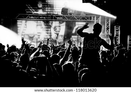 Black and White Audience Crowd Man on Shoulders Silhouette Dancing to DJ Pete Tong at Cream Nightclub Party. Nightlife Lazer Show Hands In Air With Smoke Cannon Blast - stock photo