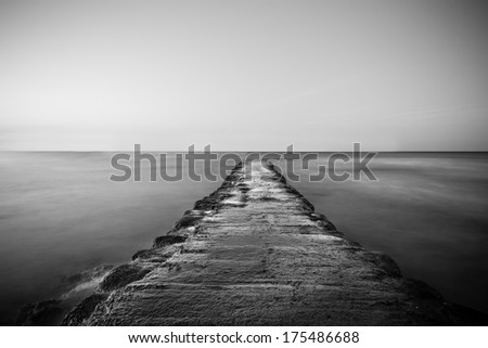 Black and white background view of a deserted old stone seawall or pier leading out over calm water receding in a straight line from the camera - stock photo
