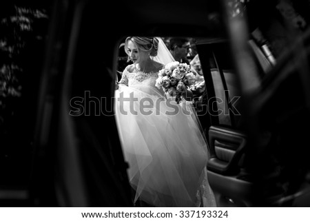 black and white Beautiful blonde wedding bride in white dress getting into elegant car - stock photo
