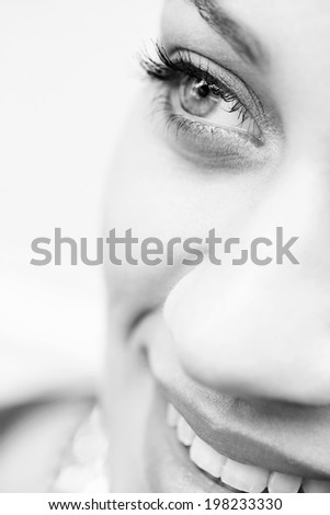 Black and white beauty close up portrait section detail of an attractive young woman looking up with clear clear eyes, wearing cosmetics and smiling. Healthy skin, beauty and sight care, well being. - stock photo