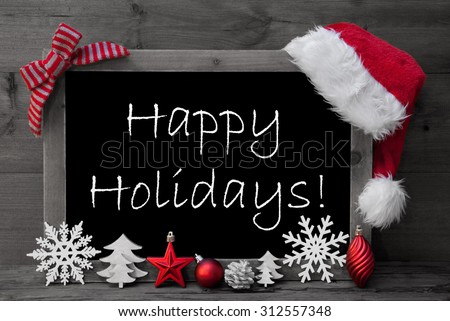 Black And White Blackboard With Red Santa Hat And Christmas Decoration like Snowflake, Tree, Christmas Ball, Fir Cone, Star. English Text Happy Holidays. Wooden Background - stock photo