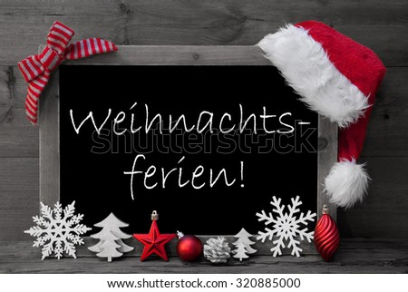 Black And White Blackboard With Red Santa Hat And Christmas Decoration like Snowflake, Tree, Christmas Ball, Fir Cone, Star. German Text Weihnachtsferien Means Christmas Holiday. Wooden Background - stock photo