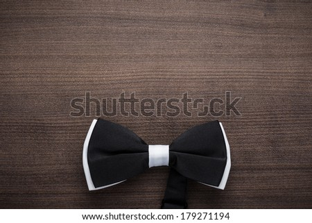black and white bow tie on wooden table - stock photo
