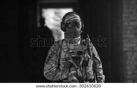 Black and White. BW. Airsoft strikeball player in military soilder uniform in action