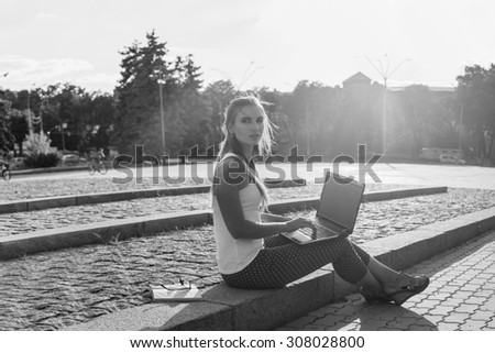 Black and White. BW. Student sitting in park near the grass working on laptop at campus