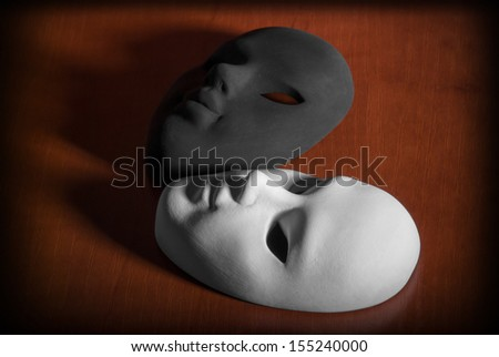 Black and white carnival mask on a wooden background.