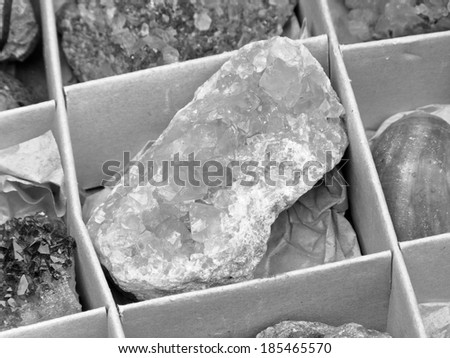 Black and white carton box with different natural gemstones  - stock photo
