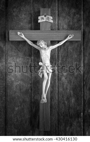 Black and white carved statue of the Crucifixion of Jesus Christ on wood  - stock photo