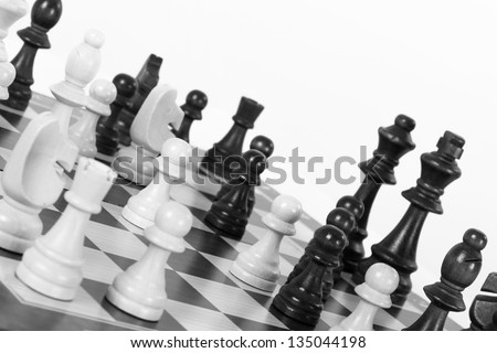 Black and white chess pieces on board, isolated on white background.