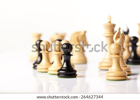 Black and white chess pieces standing on a white glass - stock photo