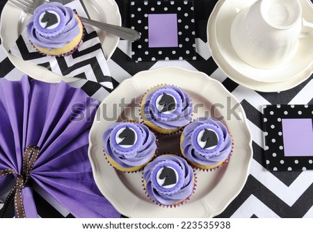 Black and white chevron with purple theme party luncheon table place setting for Melbourne Cup, Australian public holiday, horse race event - with cupcakes. - stock photo
