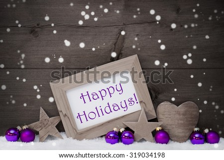 Black and White Christmas Card With Purple Christmas Decoration On White Snow, Snowflakes. Picture Frame With English Text Happy Holidays, Star, Heart And Christmas Tree Ball. Rustic Wooden Background - stock photo