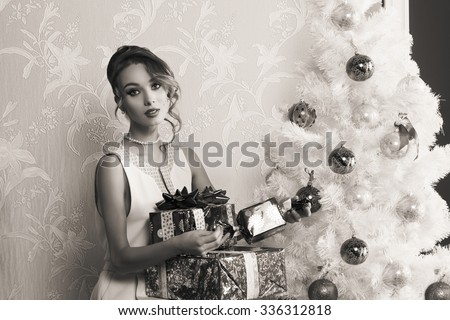 black and white Christmas portrait of stunning elegant fashion girl with some gift boxes near decorated Xmas tree