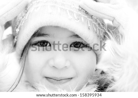 Black and white close up beauty portrait of a young child girl wearing a winter coat, woolly hat and gloves, smiling to the camera during a cold winter day, outdoors. - stock photo