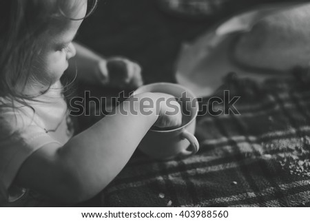 black and white close up image of a little girl playing with a drink in her cup - stock photo