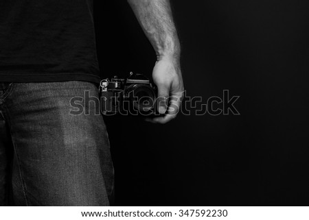 Black and white close up image of a man wearing jeans and a t shirt holding a film sir camera at his side