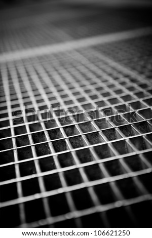 Black and white close up of a sidewalk subway grate with shallow depth of field. - stock photo