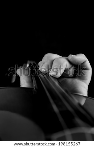 black and white close up of hand playing violin