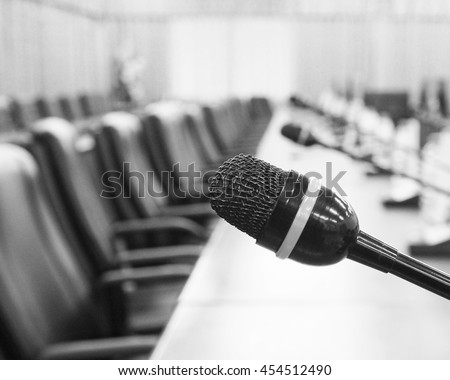 black and white close up picture of microphone in meeting room