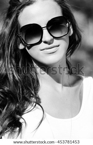 Black and white close up portrait of beautiful brunette fashion girl young woman in sunglasses white shirt smiling and looking at camera on summer outdoor background